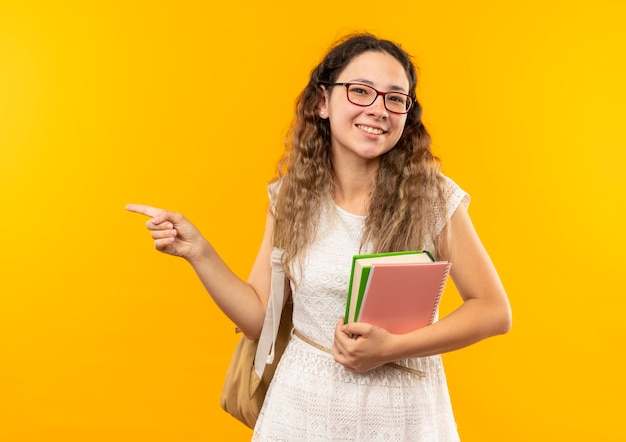 Sorridente giovane studentessa graziosa con gli occhiali e borsa posteriore che tiene il libro e il blocco note che punta sul lato isolato sulla parete gialla