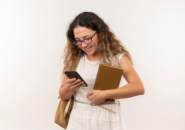 Sorridente giovane studentessa graziosa con gli occhiali e borsa posteriore che tiene il libro utilizzando il suo telefono isolato sulla parete