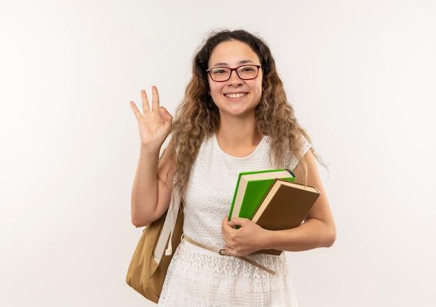 Sorridente giovane studentessa graziosa con gli occhiali e borsa posteriore in possesso di libri e facendo segno ok isolato sul muro bianco
