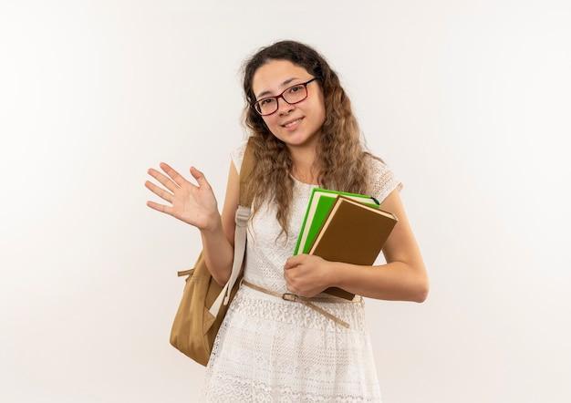 Sorridente giovane studentessa graziosa con gli occhiali e borsa posteriore in possesso di libri e gesticolando ciao isolato sul muro bianco