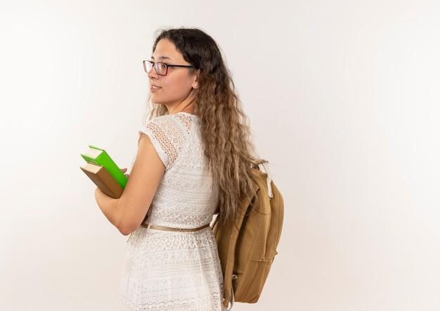 Sorridente giovane studentessa graziosa con gli occhiali e borsa posteriore che tengono i libri guardando il lato in piedi dietro la vista isolata sul muro bianco