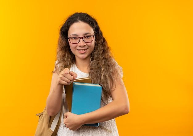 Sorridente giovane studentessa graziosa con gli occhiali e borsa posteriore che tengono i libri che indicano nella parte anteriore isolata sulla parete gialla