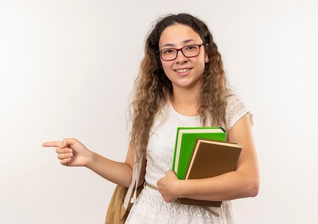 Sorridente giovane studentessa graziosa con gli occhiali e borsa posteriore che tengono i libri che indicano al lato isolato sulla parete bianca
