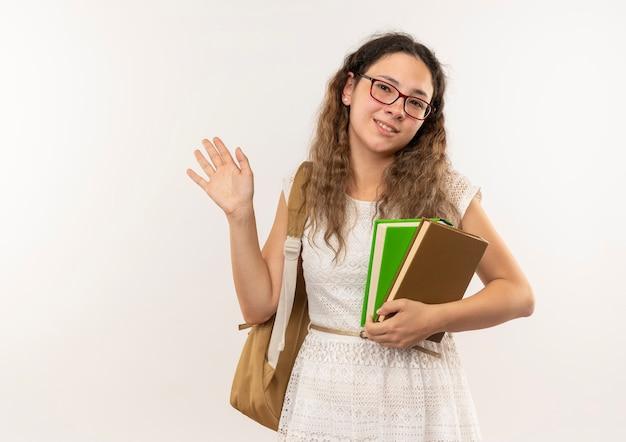 Sorridente giovane studentessa graziosa con gli occhiali e borsa posteriore in possesso di libri e salutando davanti isolato sul muro bianco