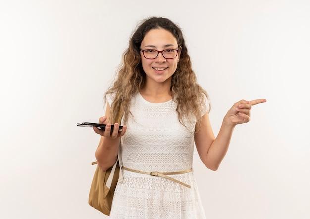 Sorridente giovane studentessa graziosa con gli occhiali e borsa posteriore che tiene il telefono cellulare rivolto verso il lato isolato sulla parete