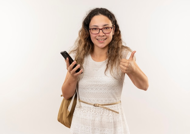 Sorridente giovane studentessa graziosa con gli occhiali e borsa posteriore che tiene il telefono cellulare e che mostra il pollice in su isolato sulla parete