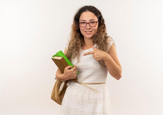 Sorridente giovane studentessa graziosa con gli occhiali e borsa posteriore che tiene e che indica i libri isolati sulla parete