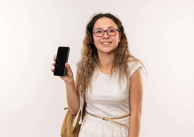 Sorridente giovane studentessa graziosa con gli occhiali e borsa posteriore che mostra il telefono cellulare isolato sul muro bianco