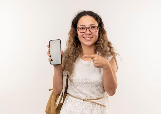Sorridente giovane studentessa graziosa con gli occhiali e borsa posteriore mostrando e indicando il telefono cellulare isolato sul muro bianco