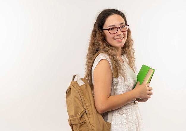 Sorridente giovane studentessa graziosa con gli occhiali e borsa posteriore in piedi nella vista di profilo che tiene libri isolati sul muro bianco