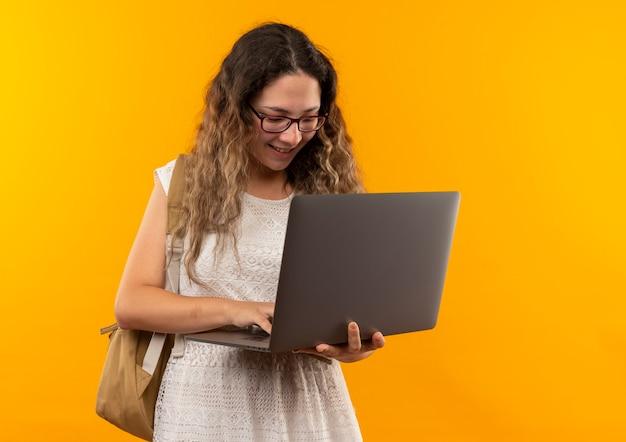 Sorridente giovane studentessa graziosa con gli occhiali e borsa posteriore utilizzando laptop isolato sulla parete gialla