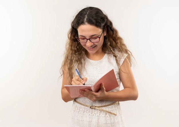 Sorridente giovane studentessa graziosa con gli occhiali e borsa posteriore scrivendo con la penna sul blocco note isolato sul muro bianco