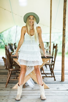 Smiling young pretty and sexy blond woman with cowboy hat and boots, in white dress, leaning on the wooden table outdoors