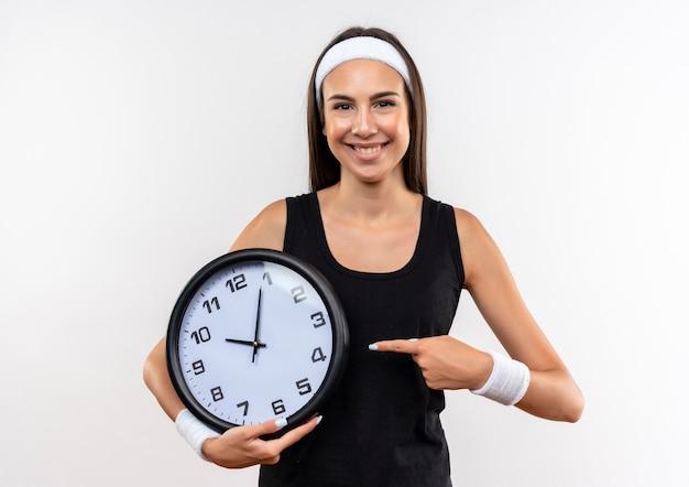 Улыбающаяся молодая симпатичная спортивная девушка с головной повязкой и браслетом, держащая и указывая на часы на белом пространстве