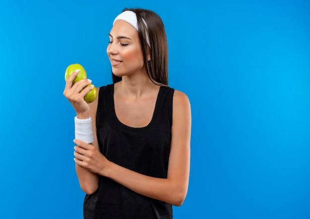 ヘッドバンドとリストバンドを身に着けている若いかなりスポーティーな女の子の笑顔は、リンゴを見て、青い空間で隔離された彼女の腕を保持しています