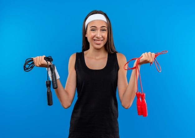 Улыбающаяся молодая симпатичная спортивная девушка с головной повязкой и браслетом держит скакалки, изолированные на синем пространстве