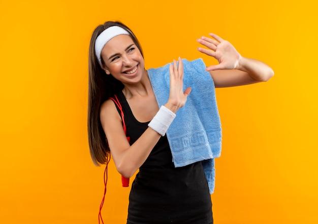 수건으로 머리띠와 팔찌를 착용하고 오렌지 공간에 손을 올리는 그녀의 어깨에 밧줄 점프를 입고 웃는 젊은 꽤 스포티 한 소녀