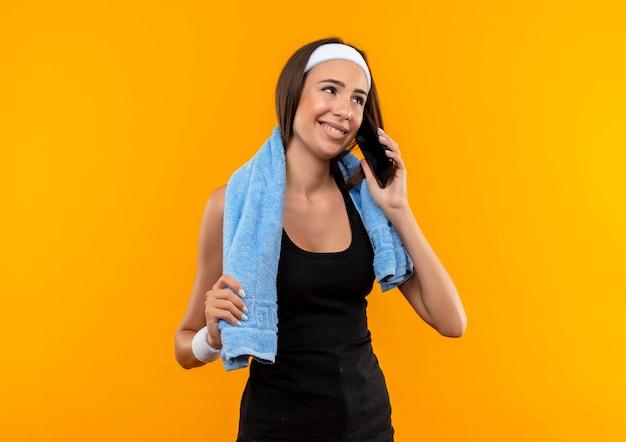 Улыбающаяся молодая симпатичная спортивная девушка с повязкой на голову и браслетом с полотенцем на шее на оранжевом пространстве