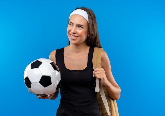 Sorridente giovane ragazza abbastanza sportiva che indossa la fascia e il braccialetto e la borsa posteriore tenendo il pallone da calcio e guardando il lato isolato sullo spazio blu