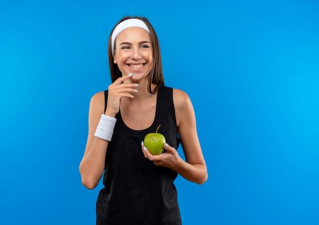 Sorridente giovane ragazza abbastanza sportiva che indossa la fascia e il braccialetto tenendo la mela guardando il lato con la mano sul mento isolato su spazio blu