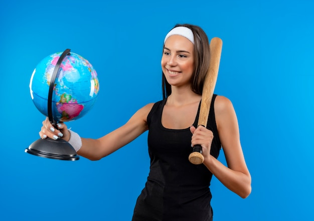 Smiling young pretty sporty girl wearing headband and wristband holding baseball bat and globe looking at globe isolated on blue space
