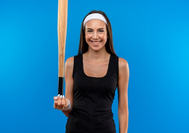Smiling young pretty sporty girl wearing headband and wristband holding baseball bat isolated on blue space