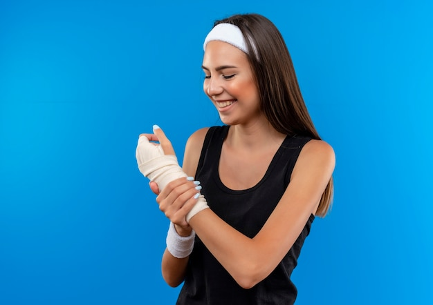 Smiling young pretty sporty girl wearing headband and wristband holding and looking at her injured wrist in bandage isolated on blue space