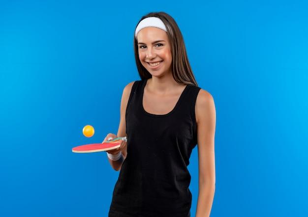 Sorridente giovane ragazza abbastanza sportiva che indossa la fascia e il braccialetto che tiene la racchetta da ping pong con la palla sullo spazio blu