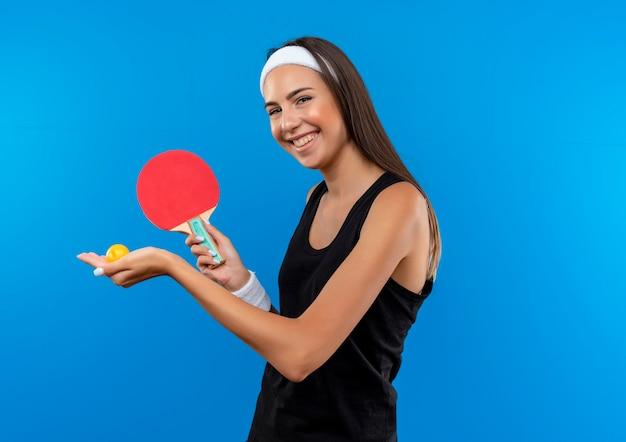 Sorridente giovane ragazza abbastanza sportiva indossando la fascia e il braccialetto che tiene le racchette da ping pong e la palla sullo spazio blu