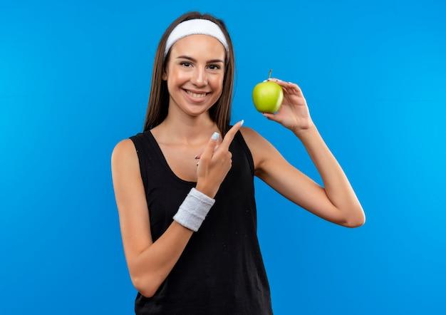 Sorridente giovane ragazza abbastanza sportiva indossando la fascia e la tenuta del braccialetto e indicando la mela isolata sullo spazio blu