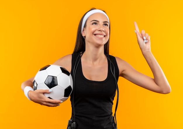 Sorridente giovane ragazza abbastanza sportiva che indossa la fascia e il braccialetto tenendo il pallone da calcio con la corda di salto intorno al collo isolato su uno spazio arancione