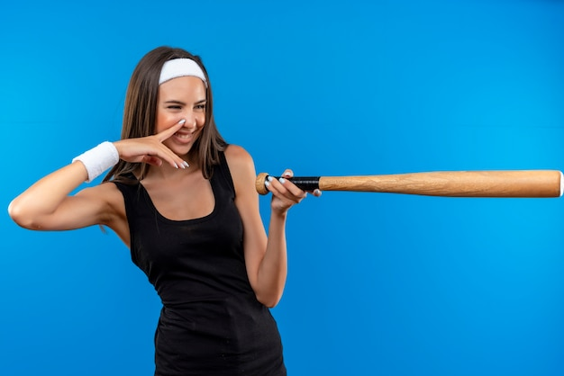 Smiling young pretty sporty girl wearing headband and wristband looking and pointing at side with baseball bat with finger on her nose isolated on blue space
