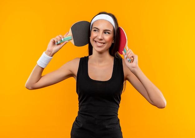 Sorridente giovane ragazza abbastanza sportiva che indossa la fascia e il braccialetto che tocca la sua testa con le racchette da ping pong e guardando il lato isolato sullo spazio arancione