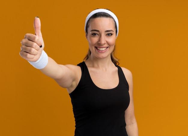 Sorridente giovane ragazza abbastanza sportiva che indossa fascia e braccialetti che mostrano pollice in su