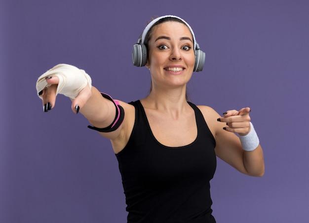 Улыбающаяся молодая симпатичная спортивная женщина с повязкой на голову, наушниками и повязкой для телефона с травмированным запястьем, перевязанным повязкой, смотрит и указывает вперед, изолированную на фиолетовой стене