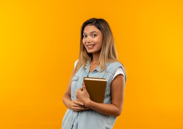 オレンジ色の壁に分離された本を保持しているバックバッグを身に着けている若いかわいい学生の女の子の笑顔