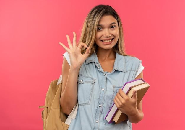 Улыбающаяся молодая симпатичная студентка в задней сумке держит книги и делает знак ок, изолированную на розовой стене