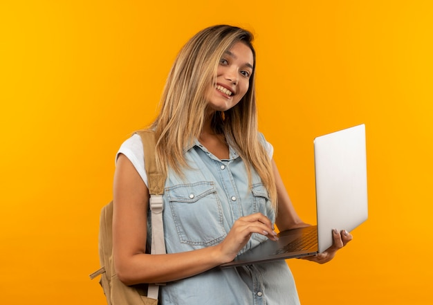 Smiling young pretty student girl wearing back bag holding and using laptop isolated on orange wall