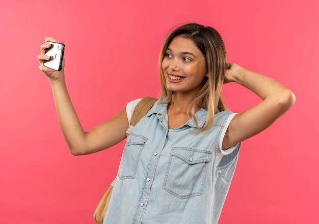 Sorridente ragazza giovane studente grazioso che indossa la borsa posteriore mettendo la mano dietro la testa e prendendo selfie isolato sulla parete rosa