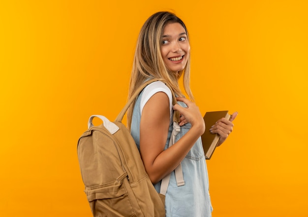 Sorridente giovane bella studentessa indossa la borsa posteriore in piedi in vista di profilo tenendo il libro e guardando dietro di lei isolato sulla parete arancione