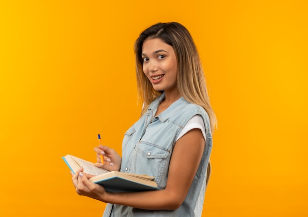 Sorridente giovane studentessa graziosa che indossa la borsa posteriore in piedi nella vista di profilo che tiene libro aperto e penna isolato sulla parete arancione