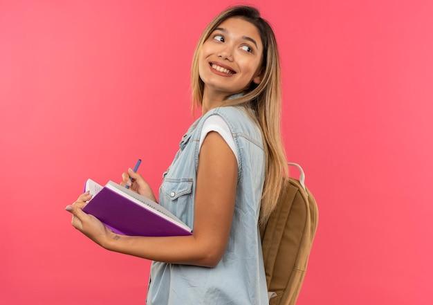 Sorridente giovane studentessa graziosa che indossa la borsa posteriore in piedi in vista di profilo tenendo il libro aperto e la penna guardando dietro isolato sulla parete rosa