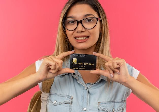 Улыбающаяся молодая симпатичная студентка в очках и задней сумке держит показывающую кредитную карту спереди, изолированную на розовой стене