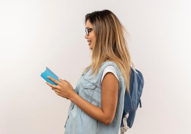 Улыбающаяся молодая симпатичная студентка в очках и задней сумке, стоящая в профиль, держа и глядя на книгу, изолированную на белой стене
