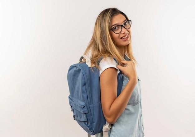 Улыбающаяся молодая симпатичная студентка в очках и задней сумке, стоящая в профиль, глядя на переднюю, изолированную на белой стене
