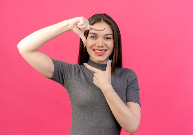 Smiling young pretty woman doing frame gesture isolated on pink background with copy space