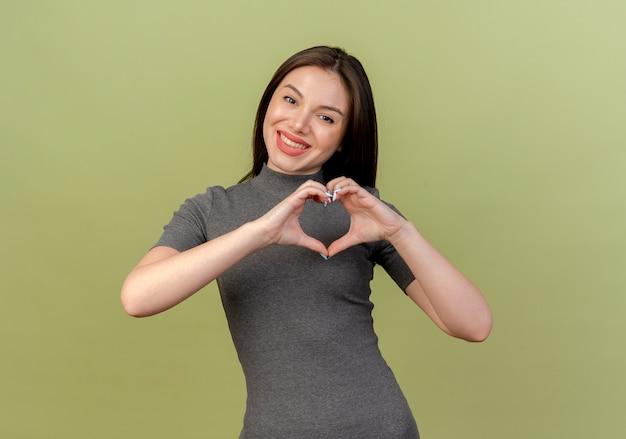 コピースペースとオリーブグリーンの背景に分離されたカメラでハートサインをしている若いきれいな女性の笑顔
