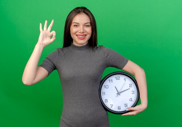 Sorridente giovane donna graziosa che tiene orologio e facendo segno ok isolato su sfondo verde