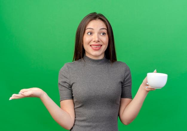 Sorridente giovane donna graziosa che tiene tazza guardando a lato e mostrando la mano vuota isolata su sfondo verde