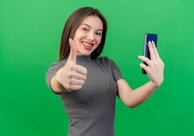 携帯電話を保持し、緑の背景に分離されたカメラに親指を表示して笑顔の若いきれいな女性